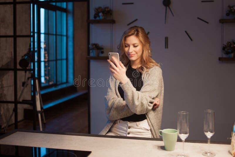 Mulher bonita nova na cozinha com smartphone Procurando a receita de cozimento em linha fotos de stock royalty free