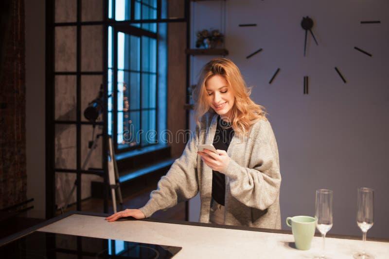 Mulher bonita nova na cozinha com smartphone Procurando a receita de cozimento em linha fotos de stock