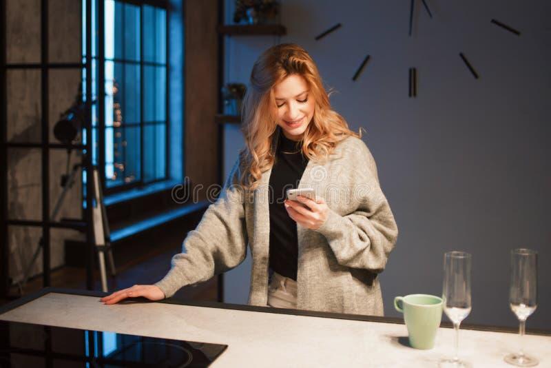 Mulher bonita nova na cozinha com smartphone Procurando a receita de cozimento em linha imagens de stock