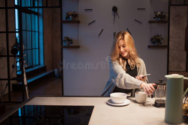 Mulher bonita nova na cozinha com smartphone Procurando a receita de cozimento em linha fotografia de stock royalty free