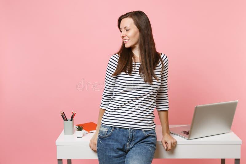 Mulher bonita nova na roupa ocasional que olha de lado o trabalho e que inclina-se na mesa branca com o portátil do PC isolado no fotografia de stock