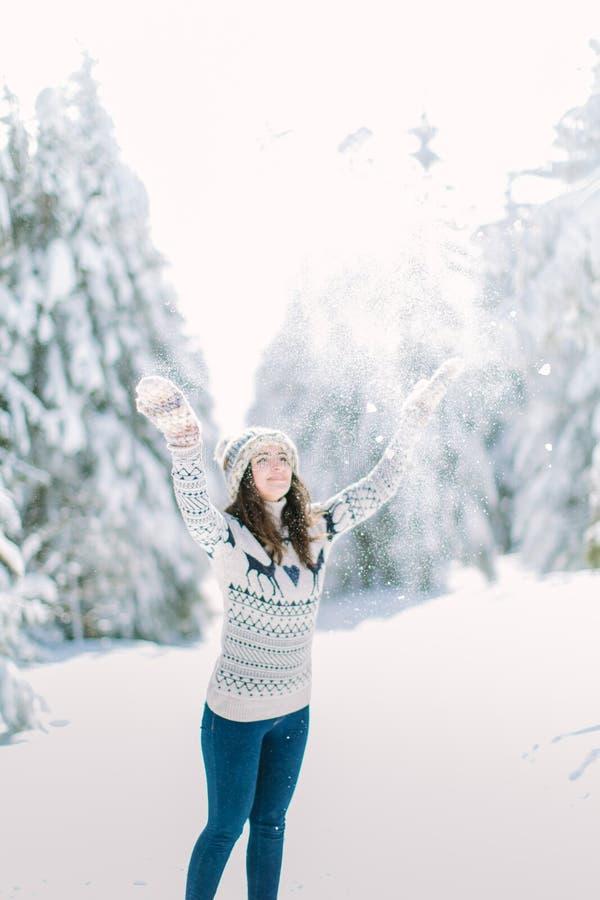 A mulher bonita nova nas calças de brim e camiseta, chapéu e luvas feitos malha joga a neve em cima Feriados de inverno, Natal, c imagem de stock
