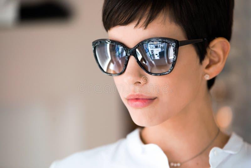 Mulher bonita nova no ótico com vidros que compra óculos de sol imagens de stock