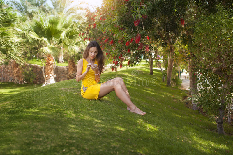 Mulher bonita nova no assento amarelo do vestido imagens de stock