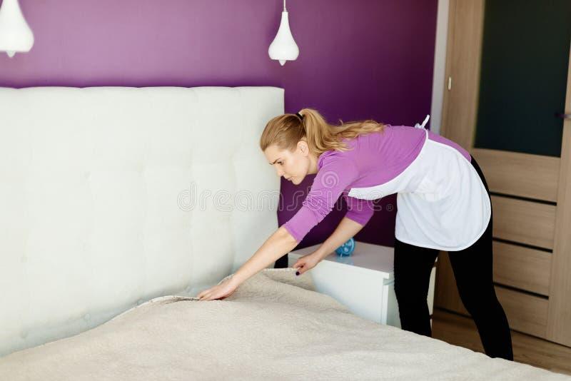 Mulher bonita nova no avental branco que faz a cama fotografia de stock royalty free