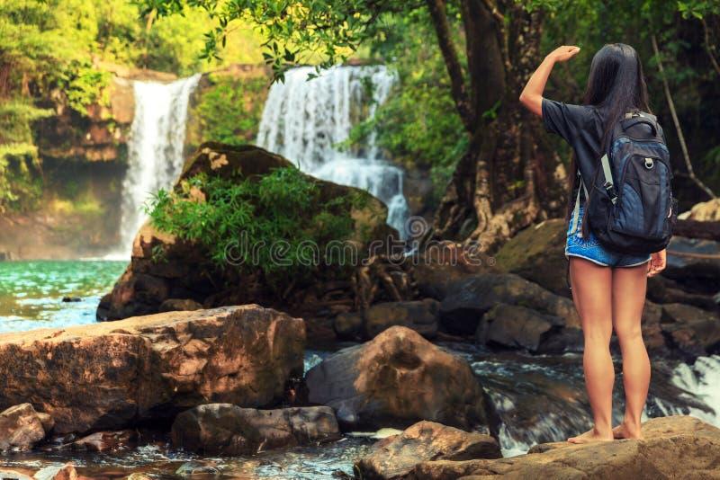 A mulher bonita nova no biquini explora a cachoeira escondida na selva tropical em natureza tropical selvagem surpreendente do fu imagem de stock