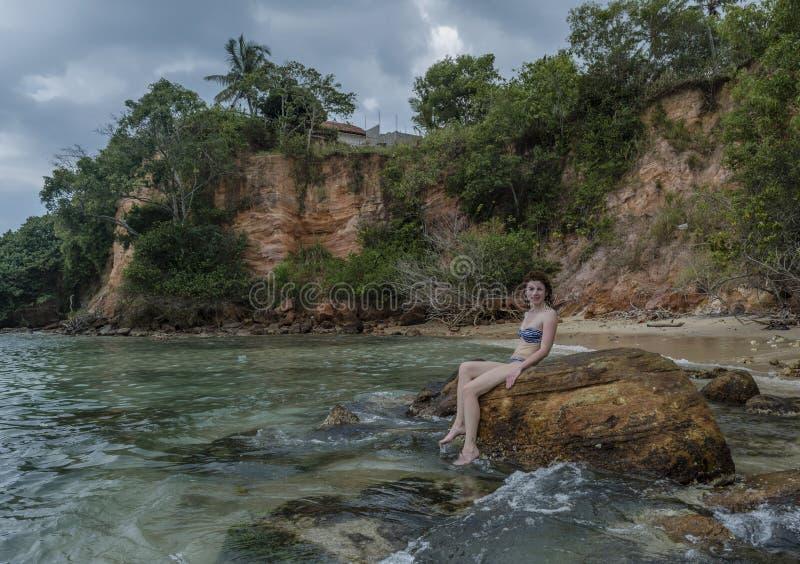 Mulher bonita nova no biquini que senta-se nas rochas na praia imagem de stock