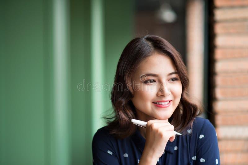 Mulher bonita nova no café perto da janela, pensando e escrevendo algo fotografia de stock
