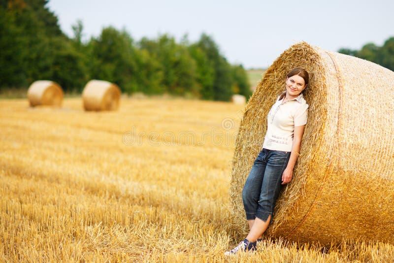 Mulher bonita nova no campo dourado amarelo do feno, Alemanha foto de stock