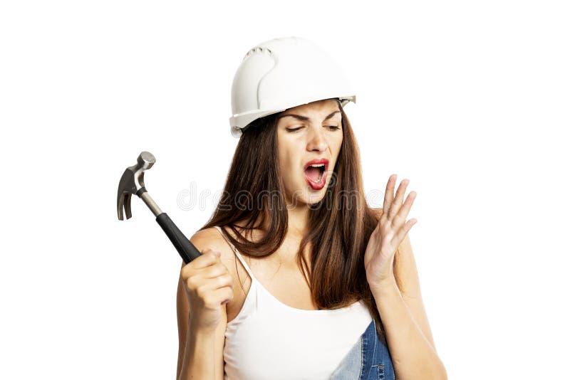 A mulher bonita nova no capacete da construção bateu com um martelo Experimentando a dor Close-up Isolado em um fundo branco foto de stock royalty free