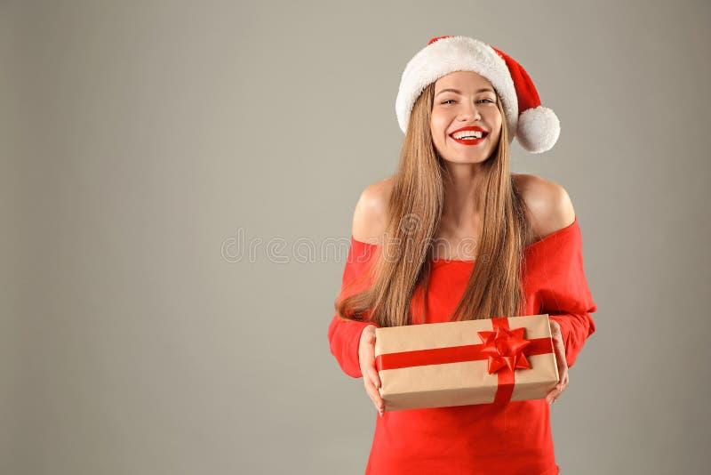 Mulher bonita nova no chapéu de Santa com caixa de presente imagens de stock