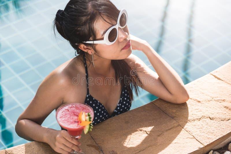 Mulher bonita nova no cockt luxuoso da bebida da piscina do biquini foto de stock royalty free