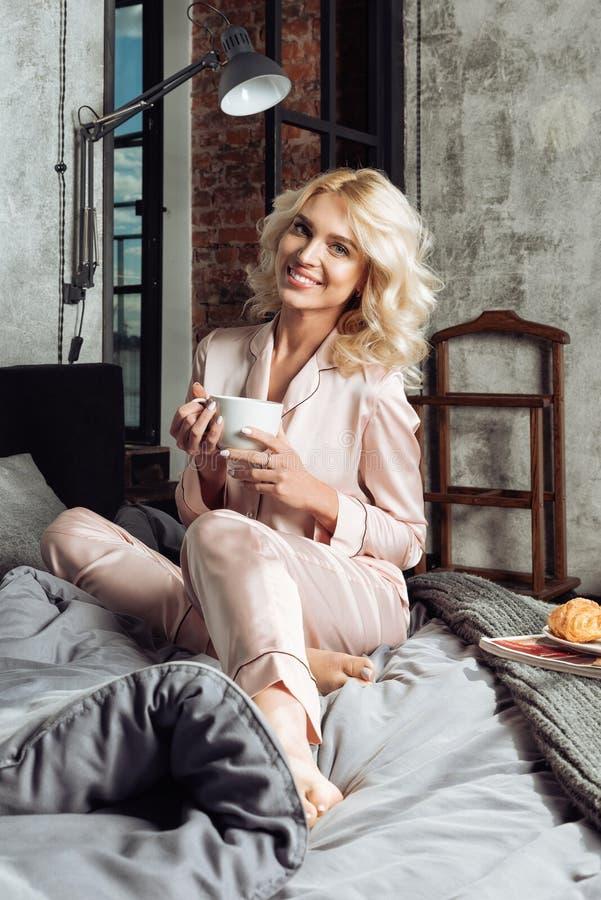 A mulher bonita nova no os pijamas cor-de-rosa de seda tem o café da manhã na cama fotografia de stock