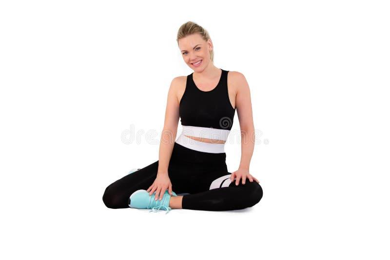 Mulher bonita nova no sportswear no estúdio na terra traseira branca - imagem foto de stock royalty free