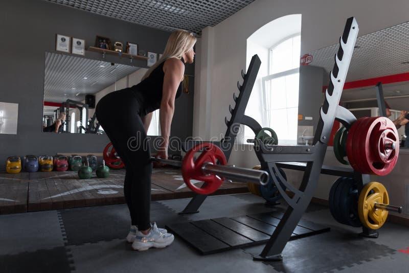 A mulher bonita nova no sportswear preto está fazendo exercícios da força com um barbell em um gym moderno Treinador atlético da  imagens de stock