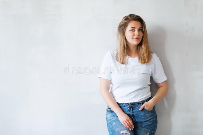 Mulher bonita nova no t-shirt e nas cal?as de brim brancos foto de stock royalty free