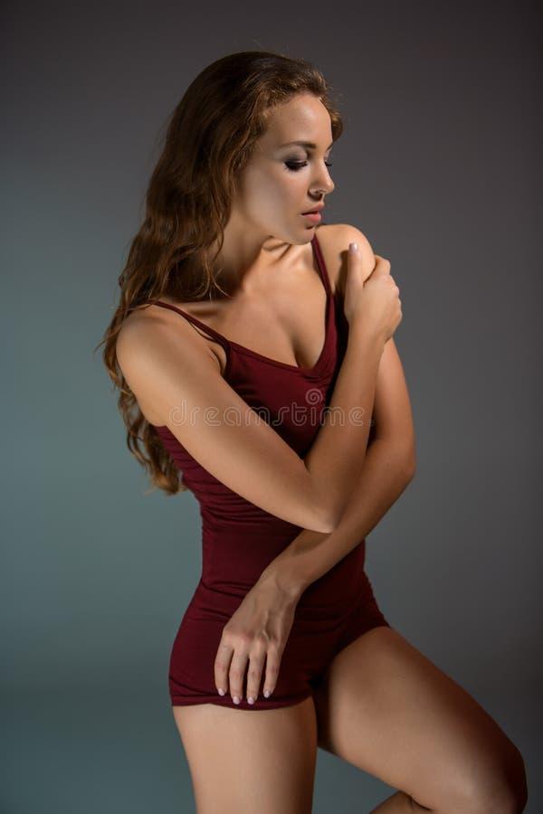 Mulher bonita nova no t-shirt vermelho e short que dança em uma obscuridade - fundo cinzento do estúdio fotos de stock royalty free
