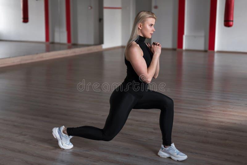 Mulher bonita nova no uniforme à moda preto desportivo no treinamento no gym Menina delgada que faz exercícios no estúdio imagem de stock