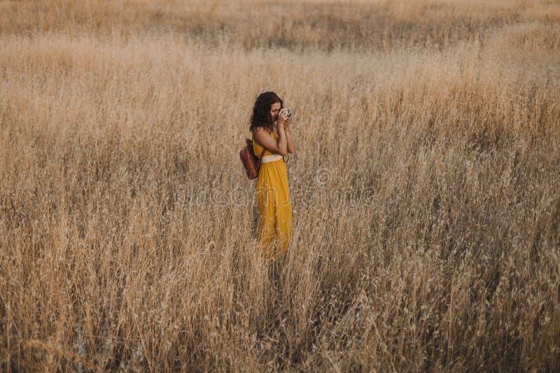 Mulher bonita nova no vestido amarelo que toma imagens com uma câmera velha do vintage Campo outdoors conceito do curso fotos de stock
