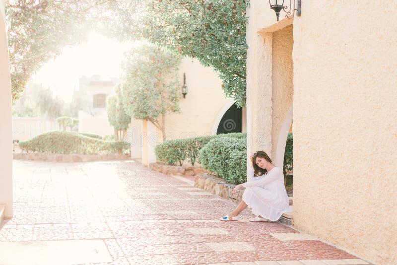 A mulher bonita nova no vestido branco est? andando na rua velha da cidade no por do sol imagens de stock