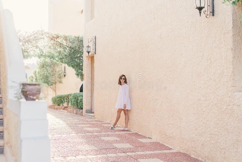 A mulher bonita nova no vestido branco est? andando na rua velha da cidade no por do sol fotos de stock royalty free