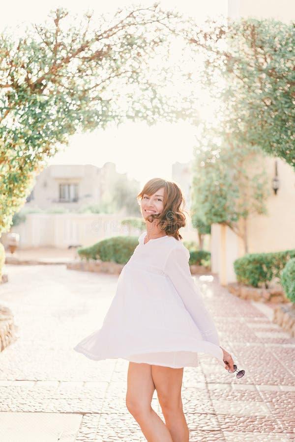 A mulher bonita nova no vestido branco est? andando na rua velha da cidade no por do sol imagem de stock