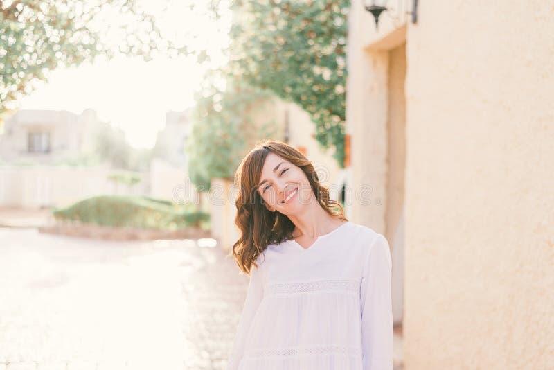A mulher bonita nova no vestido branco est? andando na rua velha da cidade no por do sol imagens de stock royalty free