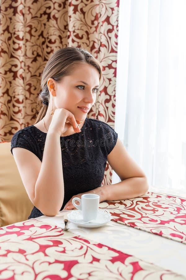Mulher bonita nova no vestido clássico preto com cabelo escuro longo em um coffe bebendo do caffe na manhã fotos de stock