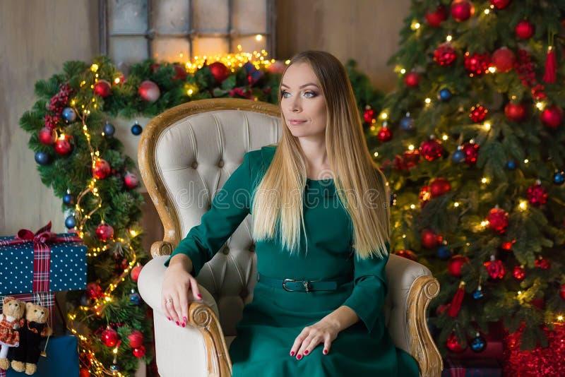 Mulher bonita nova no vestido de nivelamento elegante azul que senta-se no assoalho perto da árvore de Natal e nos presentes em u imagens de stock royalty free