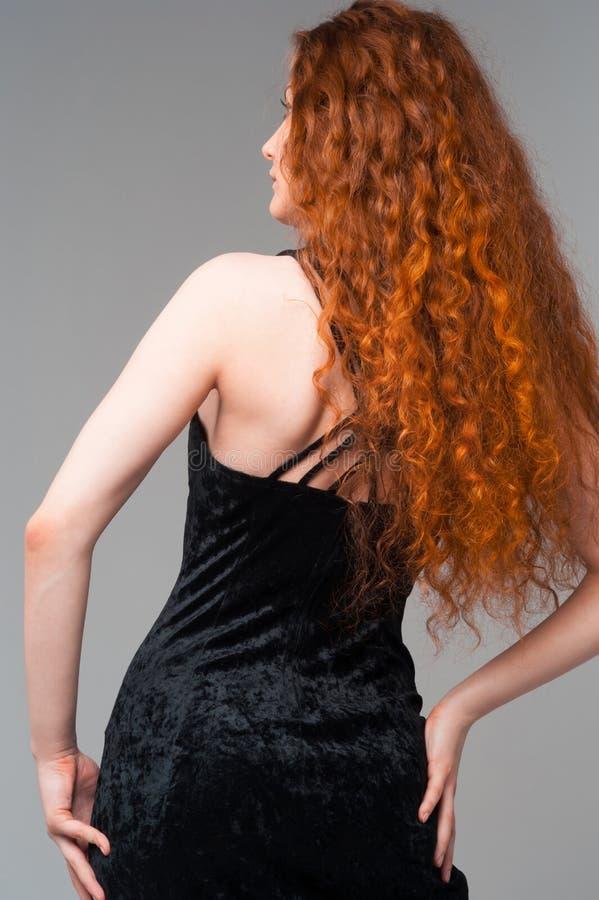 Mulher bonita nova no vestido preto com touchin vermelho longo dos cabelos imagens de stock royalty free