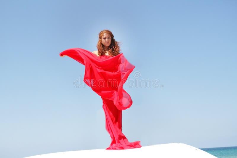 Mulher bonita nova no vestido vermelho sobre bly o céu fotografia de stock