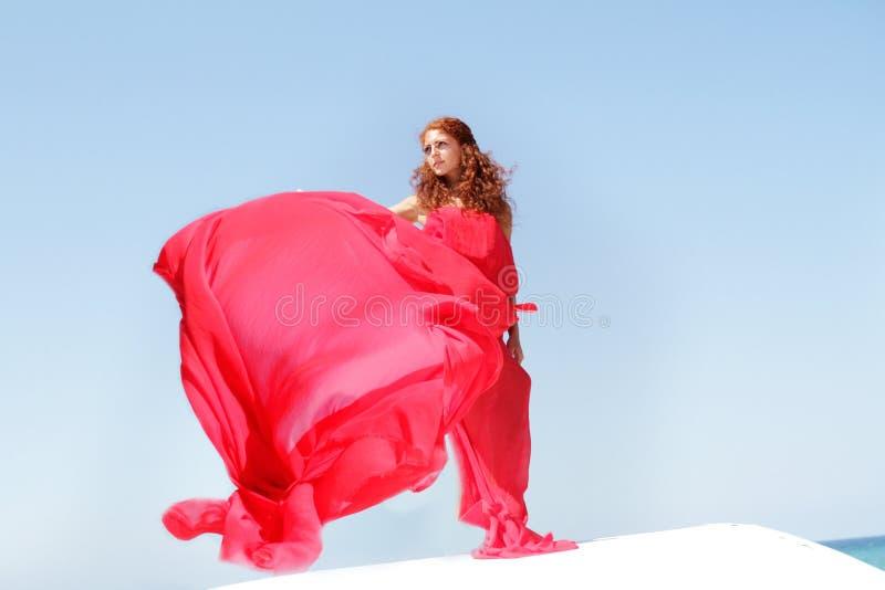 Mulher bonita nova no vestido vermelho sobre bly o céu fotografia de stock royalty free