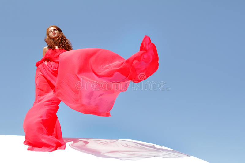 Mulher bonita nova no vestido vermelho sobre bly o céu imagens de stock royalty free