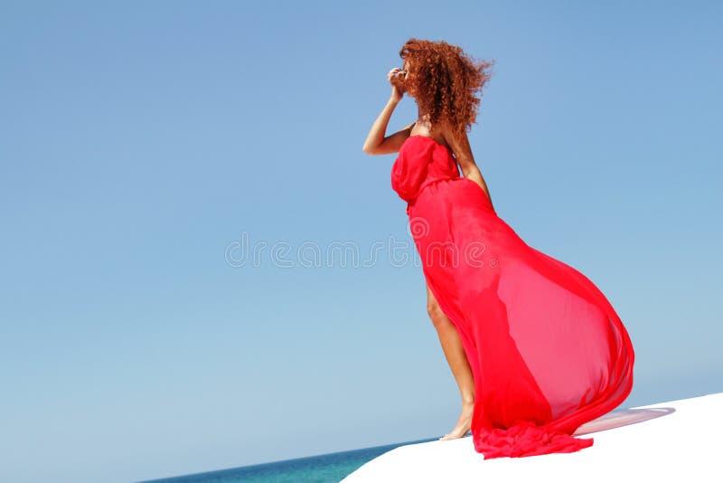 Mulher bonita nova no vestido vermelho sobre bly o céu imagem de stock royalty free