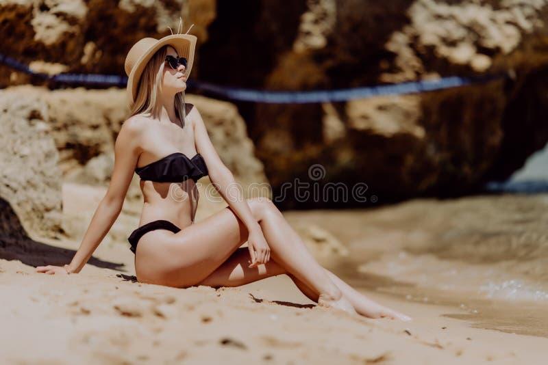 Mulher bonita nova nos óculos de sol e no chapéu do biquini que encontram-se na areia na praia tropical imagens de stock