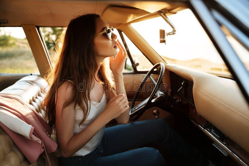 A mulher bonita nova nos óculos de sol que fixam a compõe fotos de stock