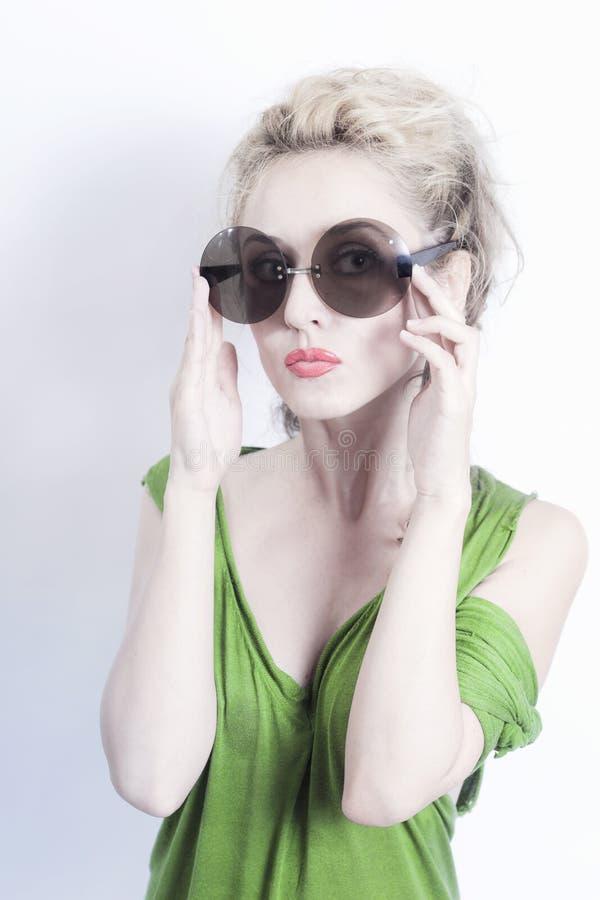 Mulher bonita nova nos óculos de sol redondos no backgroun claro foto de stock royalty free