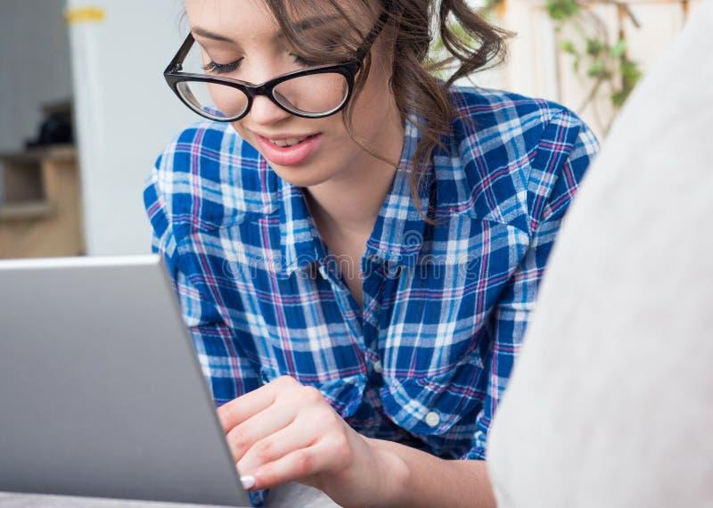 Mulher bonita nova nos monóculos usando um laptop em casa fotos de stock royalty free