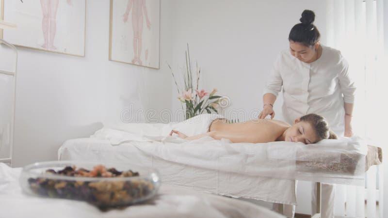 Mulher bonita nova nos termas que recebem o procedimento da medicina tibetana imagem de stock