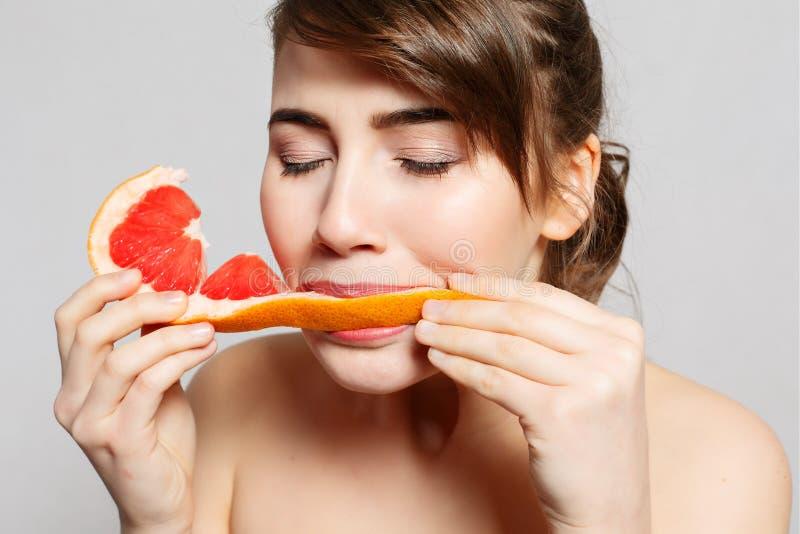 A mulher bonita nova ou a menina 'sexy' bonito com cabelo longo guardam a fatia do fruto da toranja fotografia de stock royalty free