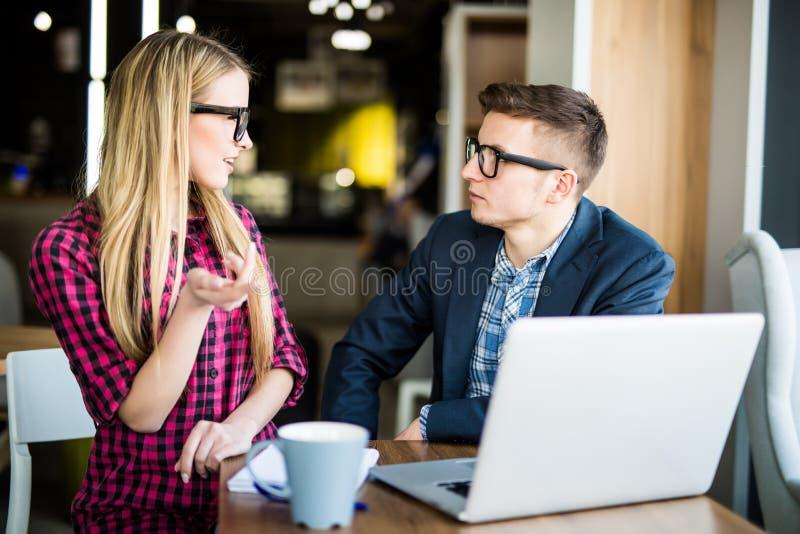 A mulher bonita nova pergunta a homem no portátil com sorriso e discussão de algo com seu colega de trabalho ao estar no escritór fotografia de stock