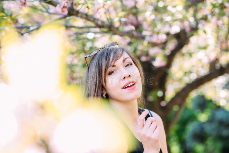 Mulher bonita nova perto da árvore de florescência de sakura Flores, mola e conceito cor-de-rosa da juventude imagem de stock royalty free