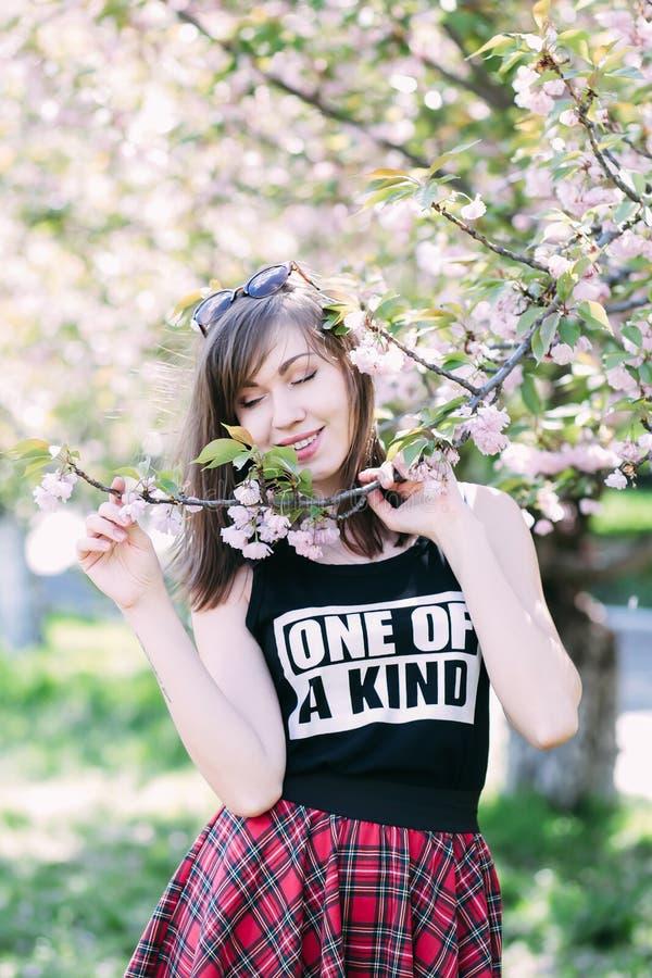 Mulher bonita nova perto da árvore de florescência de sakura Flores, mola e conceito cor-de-rosa da juventude fotos de stock royalty free