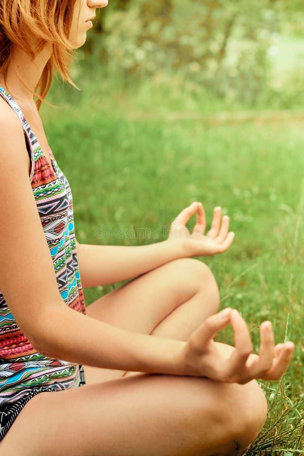 A mulher bonita nova pratica a ioga em Sunny Meadow Estilo de vida ativo Mulher da beleza que faz a ioga saudável e o conceito da foto de stock