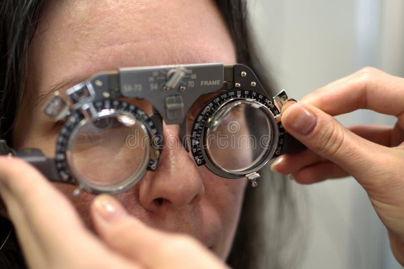 Mulher bonita nova procedimento cabendo submetido da lente no quadro de harmoniza??o de teste da lente do estilo do vintage com o foto de stock royalty free