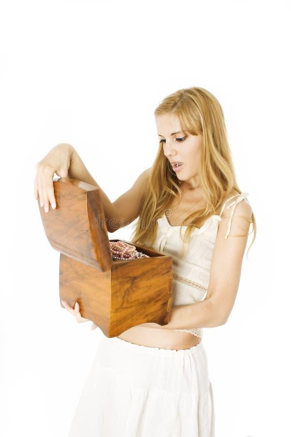 Mulher bonita nova que abre uma caixa de jóia de madeira fotografia de stock