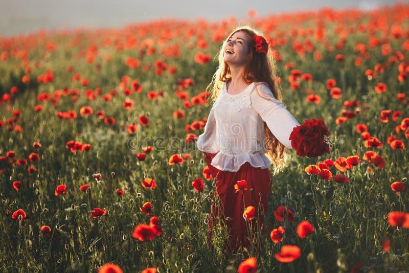 Mulher bonita nova que anda e que dança através de um campo da papoila no por do sol imagens de stock royalty free