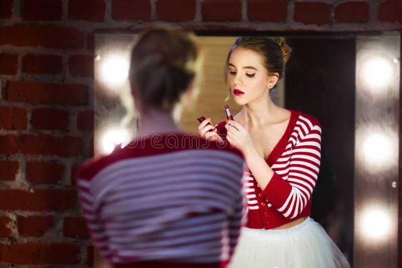 Mulher bonita nova que aplica o batom vermelho que olha o espelho foto de stock royalty free