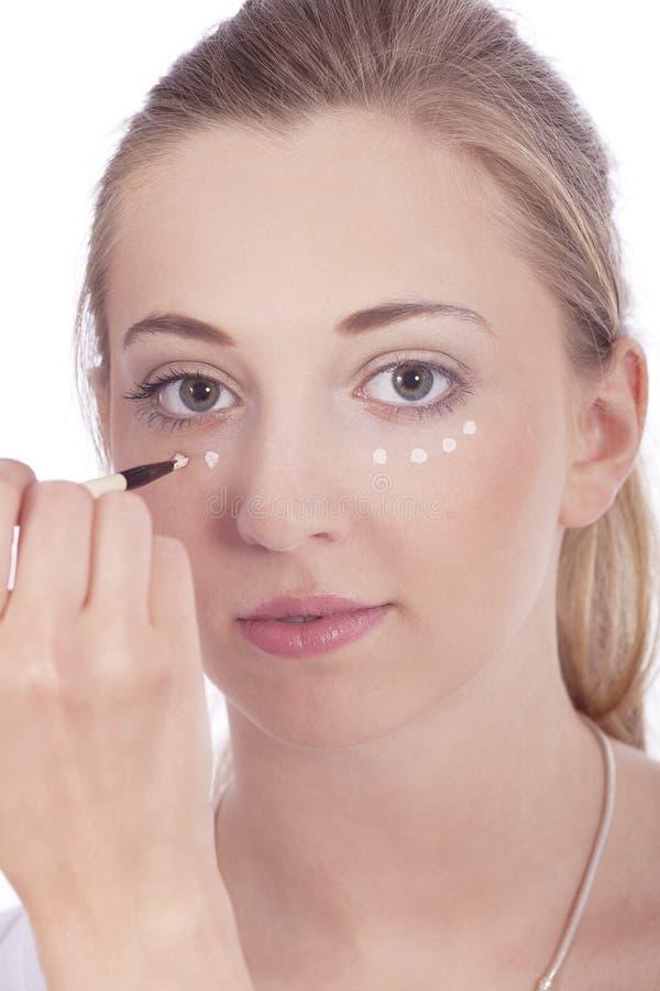 Mulher bonita nova que aplica o concealer na face fotografia de stock
