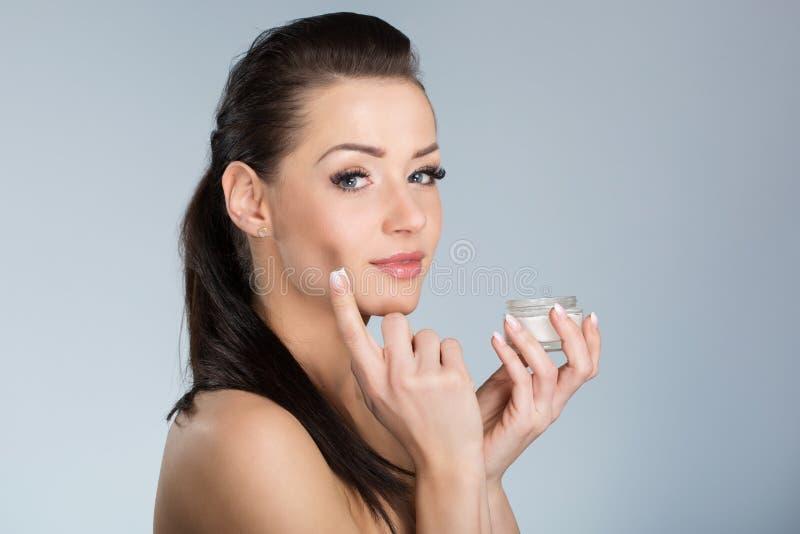 Mulher bonita nova que aplica o creme hidratando na cara imagens de stock royalty free